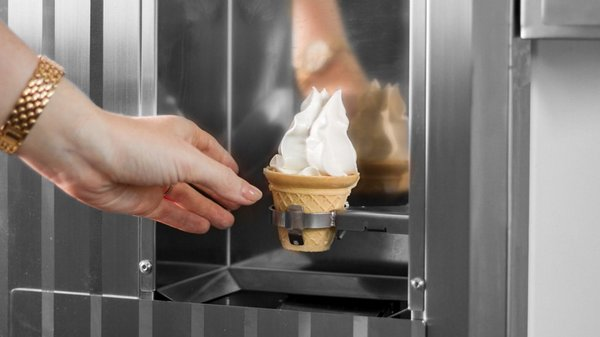 Hand reaching our for a soft ice cream from an ice cream machine